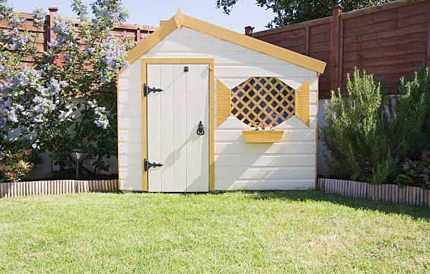 Petit abri de jardin en bois dans le jardin d'une maison