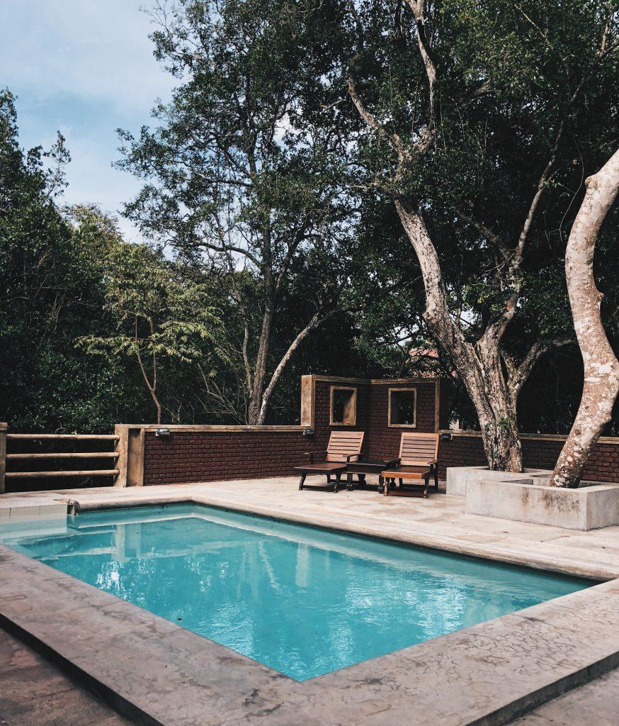 terrasse avec piscine et fauteuils en bois sous les arbres